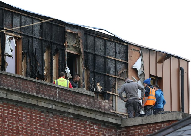 Workers clear debris around the Malone Exchange on the Lisburn Road, Belfast, where there was a fire in the building's penthouse earlier on Tuesday. Over 40 firefighters attended the scene. Picture date: Tuesday May 18, 2021.