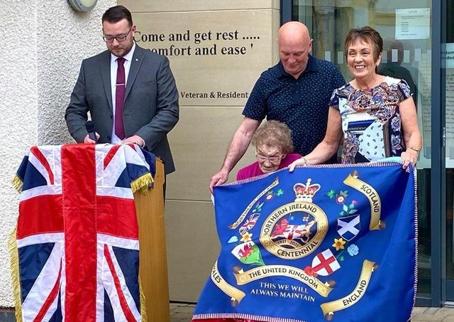 Mrs Emily Clarke being presented with the first of the LCC's NI Centenary flags at the Somme Nursing Home in east Belfast.