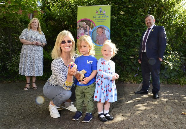 Health Minister Robin Swann with the Chief Executive of the Northern Ireland Childminder Association (NICMA), Patricia Lewsley-Mooney and childminder Joan Boyd with Henry and Margo