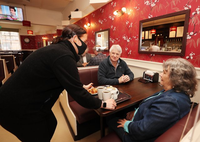 COVID-19 lockdown restrictions are further eased across Northern Ireland.  Cafes, bar and restaurants can now cater for indoor service with Cinemas also reopening.  Jack and Margaret Larkin are served by Gemma Burns at SD Bells Tea & Coffee house on the Newtownards Road in east Belfast. Picture by Jonathan Porter/PressEye