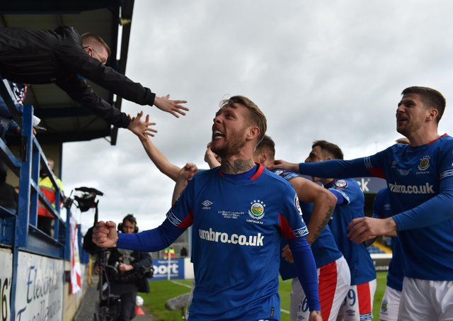 Kirk Millar and Linfield players share in the celebrations with supporters inside Mourneview Park. Pic by Pacemaker.