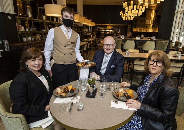 Northern Ireland Economy Minister Diane Dodds (left) welcomes the reopening of indoor hospitality at the Grand Central Hotel in Belfast with Janice Gault (right) of the Northern Ireland Hotels Federation (NIHF) and General Manager Stephen Meldrum (second from right) as they are being served  the hotel's house breakfast by Conor Sullivan.