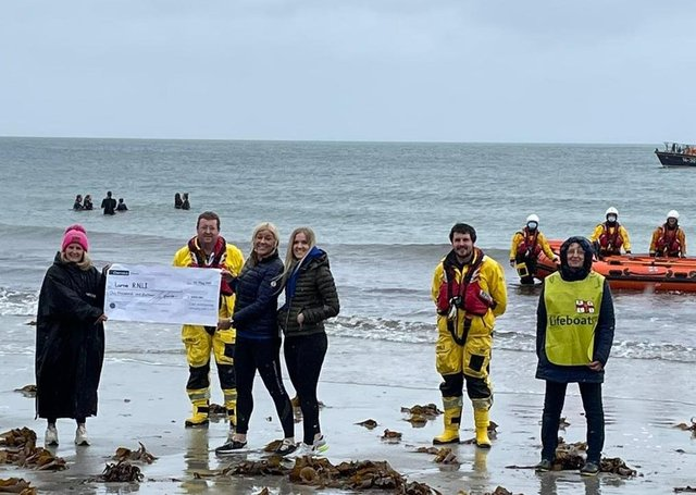 Some of Larne RNLI's volunteer crew and members of the fundraising team are presented with a cheque for £1,016 by the Chilli Dippers at Ballygally beach