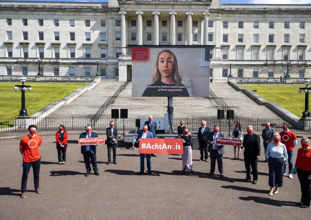 An Dream Dearg spokesperson Padraig O Tiarnaigh (left), and An Dream Dearg spokesperson Conchur O Muadaigh (second from right) stand with MLAs from Sinn Fein at Stormont as members of the Irish Language Community display an outdoor mobile screen with a message featuring over 70 Irish language speakers calling upon the Northern Ireland Executive along with the British and Irish Governments to implement the New Decade, New Approach (NDNA) deal, legislation regarding Irish language rights, 500 days after the agreement. Picture date: Tuesday May 25, 2021. PA Photo. See PA story ULSTER Language. Photo credit should read: Liam McBurney/PA Wire