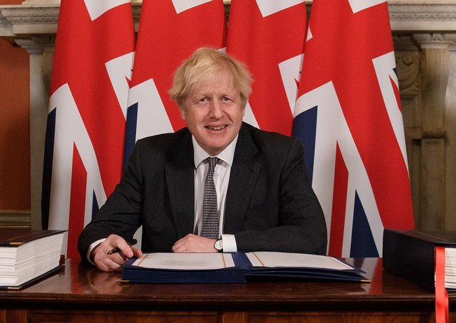 """Prime Minister Boris Johnson signs the EU-UK trade deal at 10 Downing Street last December. Clive Bleary writes: """"He has thrown down the gauntlet to us. We may not like it, and I don't, but a growing majority in Britain see us as a drain on their resources, and a threat to their security"""" Photo: Leon Neal/PA Wire"""