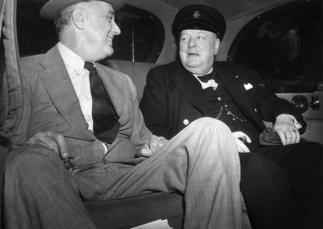 British Prime Minister Winston Leonard Spencer Churchill (1874 - 1965) with Franklin Delano Roosevelt (1882 - 1945) 32nd President of the United States, seated in a car on their way to the White House in Washington to discuss the Allied Victory in North Africa.   (Photo by Topical Press Agency/Getty Images)