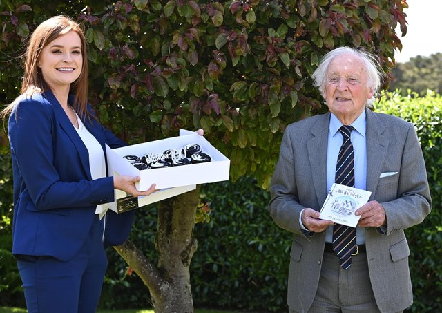 Randal Black celebrates reaching 100 with a gift from Charlotte McClean, manager of the Old Inn, Crawfordsburn, where he is a regular customer. The inn presented him with a £100 hotel voucher and birthday cupcakes to celebrate his milestone.