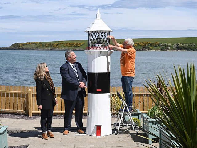 A ten-foot-tall lighthouse built by prisoners in Maghaberry will help shine a spotlight on the convalescent work of the cancer charity Hope House. The wooden structure, which took several months to construct in Maghaberry Prison, was this week relocated to Hope House Cottage on the beach at Browns Bay, Islandmagee. Looking on as charity volunteer Sam McCullough makes a final adjustment to the lighthouse, are David Savage, Governor Maghaberry Prison and Dawn McConnell, Founder of the Hope House charity. Picture: Michael Cooper