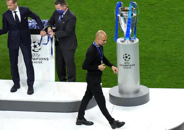 Manchester City manager Pep Guardiola with the runners up medal as he walks past the Champions League trophy at Estadio do Dragao in Porto.