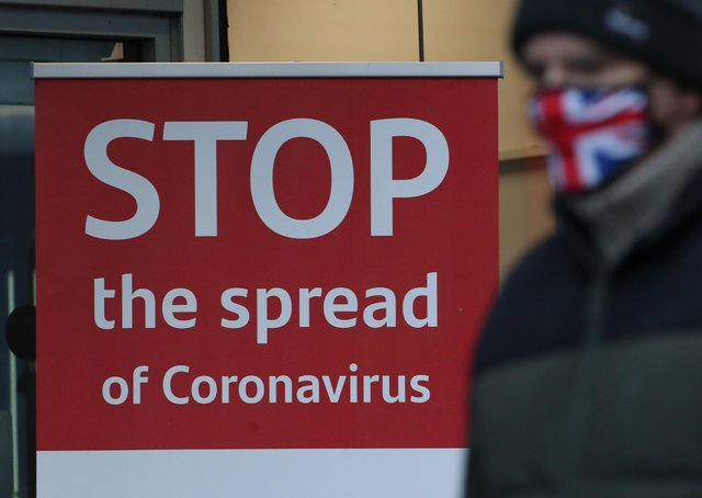 A man wearing a face mask walks past a coronavirus advice sign. Photo credit: Andrew Milligan/PA Wire