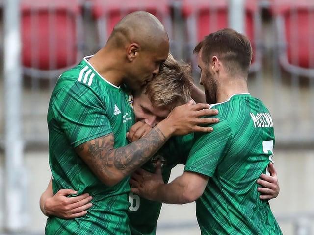 Northern Ireland's Ali McCann celebrates his goal with Josh Magennis and Niall McGinn