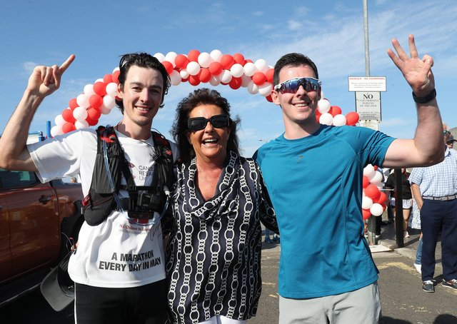 Joshua Eastwood finishes his 31st marathon in May. He's joined by his mum Gail and twin brother Jacob. Photograph by Declan Roughan