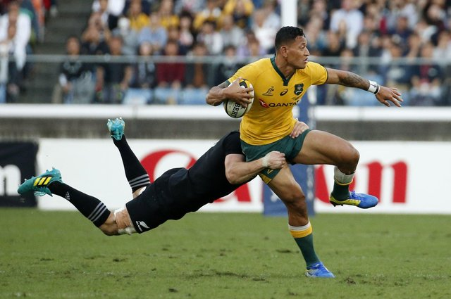 """The Australia rugby player Israel Folau, seen above being tackled in a game in 2018, was, Samuel Morrison writes, """"effectively driven out of his sport because he dared to quote one of the texts I have cited in this article"""". (AP Photo/Shuji Kajiyama)"""