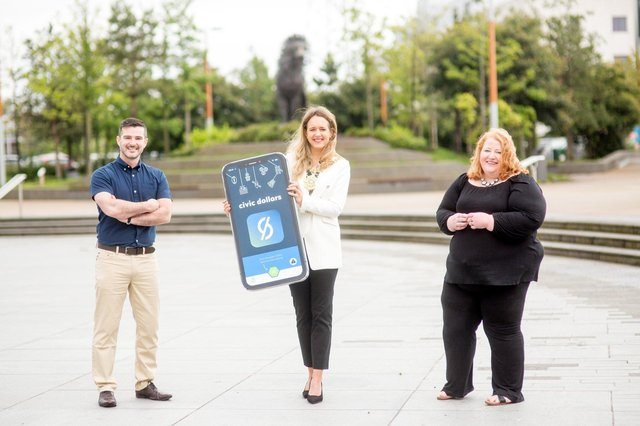 Stephen McPeake, CEO of local company Moai Digital Ltd and creator of the Civic Dollars app, Belfast Lord Mayor Councillor Kate Nicholl and Justice Minister, Naomi Long launch the new 'Civic Dollars' mobile phone app