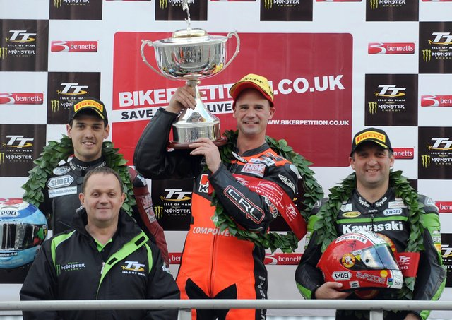 Ryan Farquhar (KMR Kawasaki) celebrates his victory in the Lightweight race at the Isle of Man TT in 2012 with runner-up James Hillier (Bournemouth Kawasaki) and Michael Rutter (KMR Kawasaki). Also included is 11 times TT winner Phillip McCallen who presented the trophy.