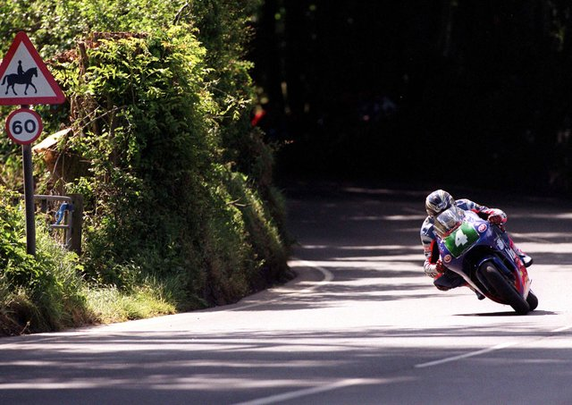 John McGuinness flies through Ballaspur on his way to victory in the Lightweight TT, his first Isle of Man win in 1999.