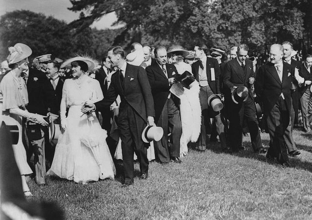 King George VI (1895-1952) and Queen Elizabeth (1900-2002) attend a garden party at the Château de Bagatelle in the Bois de Boulogne, during their State Visit to Paris, France, July 1938. On the right is French President Albert François Lebrun (1871-1950). The Queen is wearing a dress from the White Wardrobe designed for her by Norman Hartnell to mark the death of her mother, the Countess of Strathmore. Picture: Photo by Topical Press Agency/Hulton Archive/Getty Images