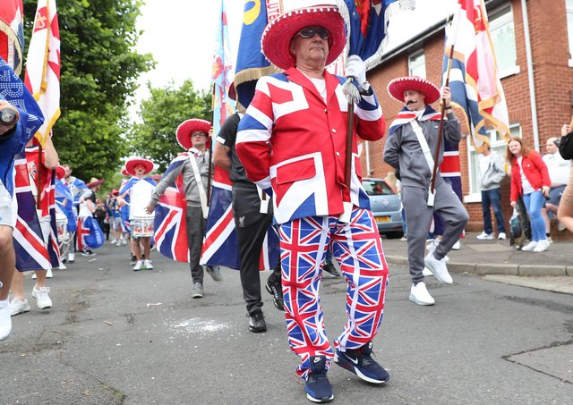 Dressed for the occasion as he leads the First Ulster Flute Band around the Sandy Row of Belfast on July 12, 2020