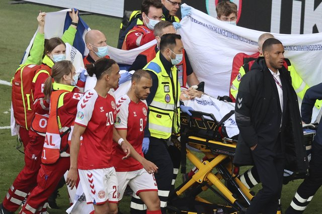 Denmark's Christian Eriksen (hidden) leaving the pitch on Saturday after life-saving pitchside treatment. Pic by PA.