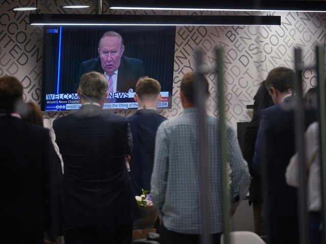 Staff in the green room watching a television screen showing presenter Andrew Neil broadcast from a studio, during the launch event for new TV channel GB News at The Point in Paddington, London