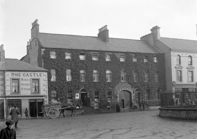 A busy street scene in Lurgan, Co Armagh, with a pub, an hotel, pedestrians, police and a well loaded horse and cart on display. The photographer was taken by Fergus O'Connor and it is part of the National Library of Ireland Fergus O'Connor Collection. NLI Ref: OCO 158. Picture:  National Library of Ireland