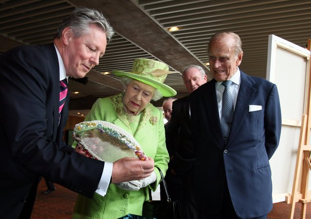 Peter Robinson as first minister shows the Queen and Prince Philip a gift at the Lyric Theatre in Belfast, with the deputy first minister Martin McGuinness looking on, in June 2012, on the Queen's jubilee visit