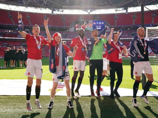 Brad Lyons (far left) celebrates Morecambe's play-off win over Newport County