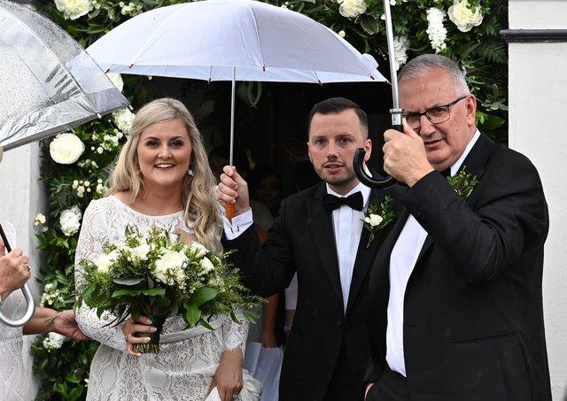 Laura and Philip Kennedy on their wedding day at Banbridge Road Presbyterian Church in Dromore today with Philip's father Danny Kennedy. Pic by Colm Lenaghan/Pacemaker