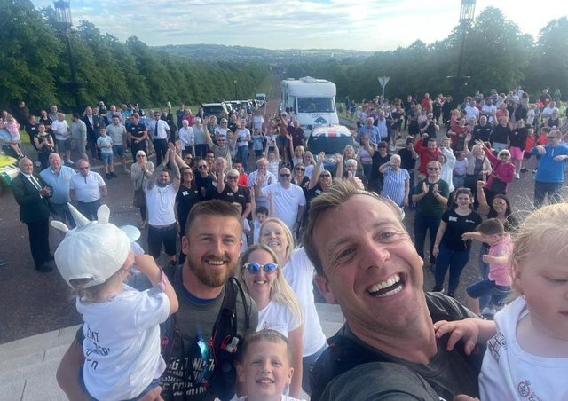 Ian Reid (left) and Connor Ferguson (right) celebrate with friends and family as they finish their 420 mile trek at Parliament Buildings in support of Beyond the Battlefield.