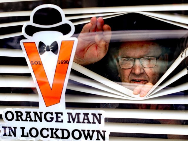 Orange Man, Randy Davidson, who had to isolate at home in 2020, poses with a sticker in his window to celebrate the 12th of July as traditional large-scale parades were cancelled due to the pandemic.