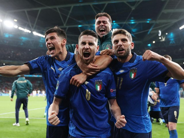 Jorginho (C) celebrates with teammates after scoring the winning penalty against Spain