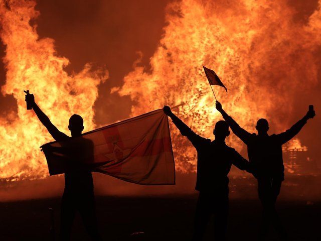 People celebrate the burning of the Eleventh night bonfire in Portadown.