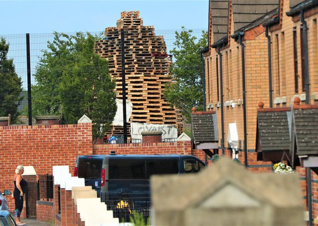 A woman looks at the loyalist bonfire, built in the loyalist Tiger's Bay area, from nationalist New Lodge area in north Belfast