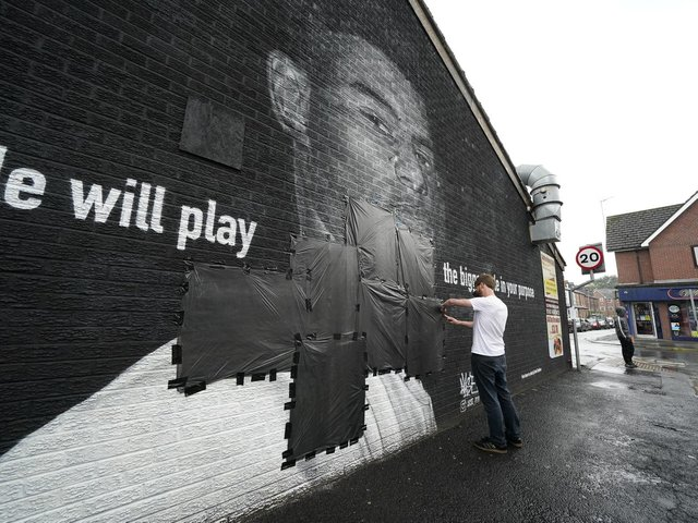 Ed Wellard, from Withington, tapes bin liners across offensive wording on the mural of Manchester United striker and England player Marcus Rashford on the wall of the Coffee House Cafe on Copson Street, Withington, which appeared vandalised the morning after the England football team lost the UEFA Euro 2021 final.