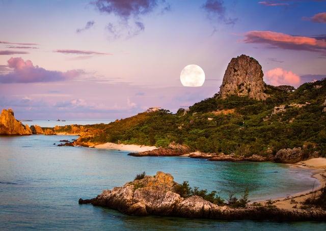 The moon over a coastal landscape, Okinawa, Japan.