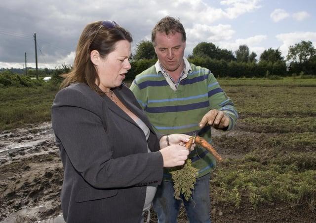 DARD Minister Michelle Gidernew surveys the effects of flooding on the farm of John Sloane near Lisburn in August 2008. Picture: Darryl Mooney/Mooney Media/Farming Life archives