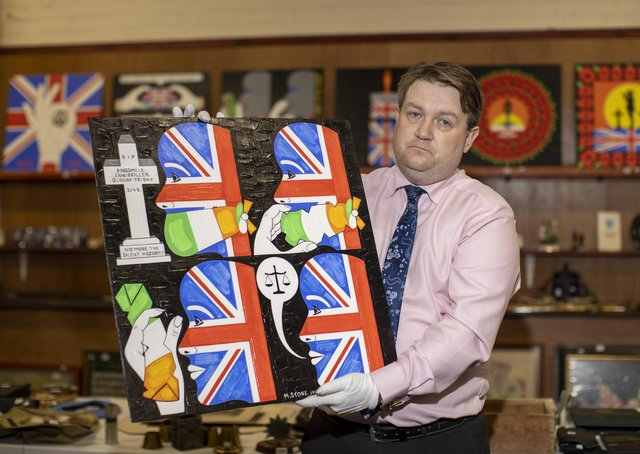 Auctioneer Carl Bennett holding art by Michael Stone, one of the lots for sale at Bloomfield Auctions in east Belfast next week. Picture date: Monday September 20, 2021.